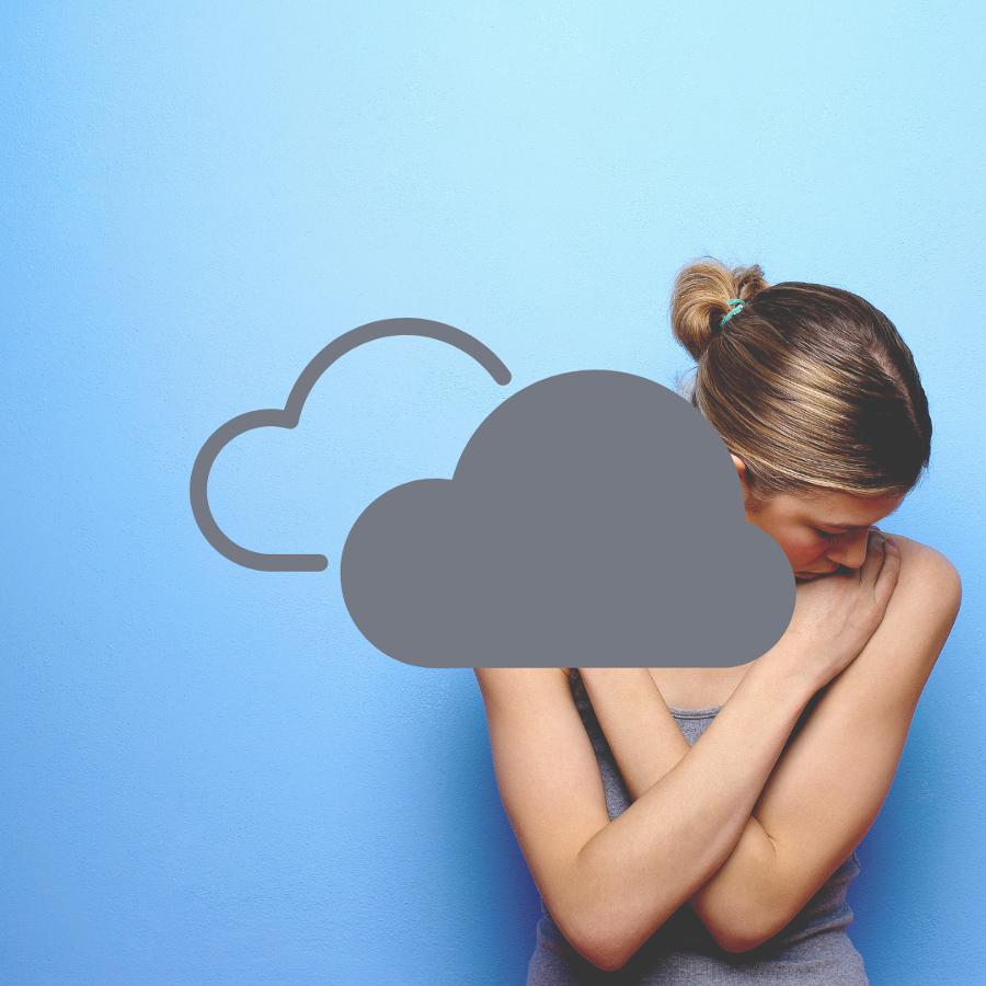 Nainen käpertyneenä, katse alas luotuna. Naisen edessä on harmaa pilvi. Tausta on puhtaan sininen.