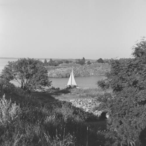 Mustavalkoinen kuva vuodelta 1955. Pieni purjelaiva kulkee Suomenlinnan väylässä. On kesä. Kuvaaja Volker von Bonin.